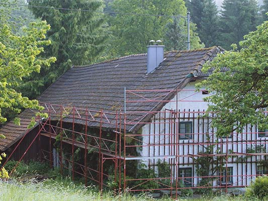 Old roof on a rural cottage (with scaffolding) just before the roof was renovated with PREFA shingles