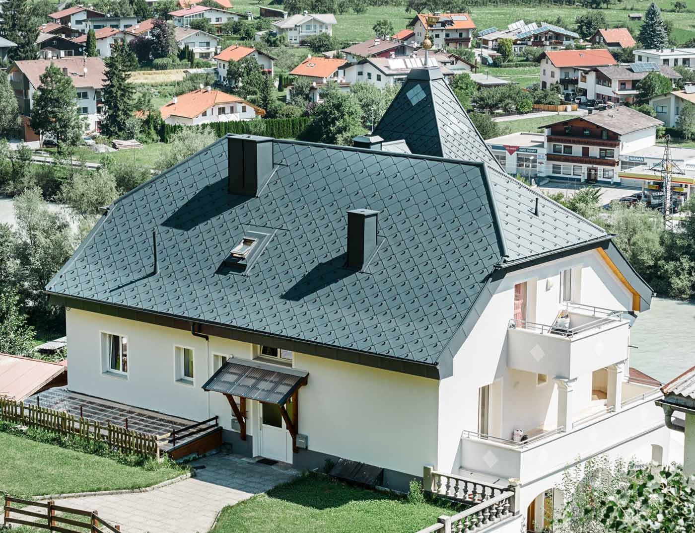 Half-hip roof with a tower, covered with the 44 × 44 aluminium rhomboid roof tiles in anthracite.