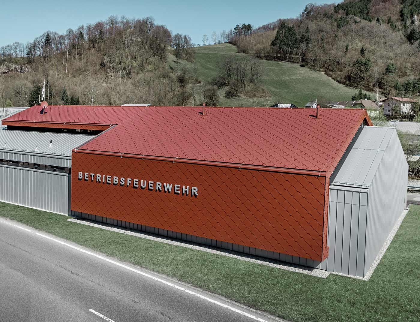 The new fire station for PREFA and Neuman Aluminium's own fire brigade was clad with the new 44 × 44 rhomboid roof and wall tiles in P.10 oxide red and Prefalz in metallic silver.