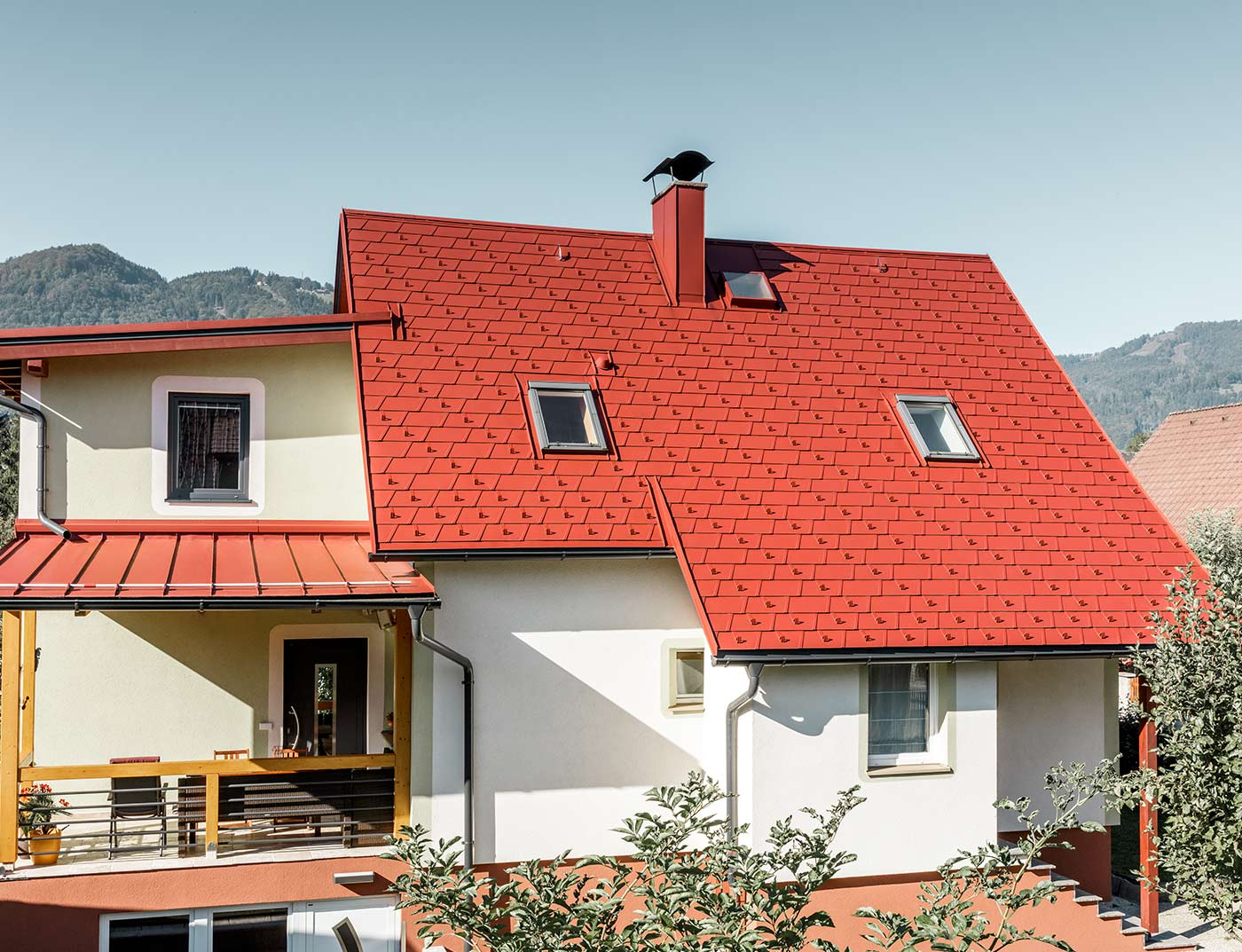 Classic single-family house with two skylights and chimney, roofed with the new PREFA DS.19 shingle in P.10 oxide red.